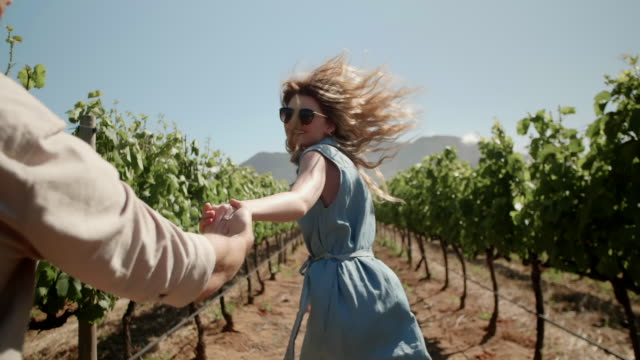 Young couple running through grape vines holding hands