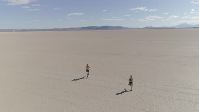 Young couple running through the dessert video