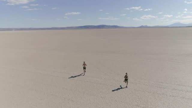 ungt par kör genom dessert - kameraåkning på räls bildbanksvideor och videomaterial från bakom kulisserna