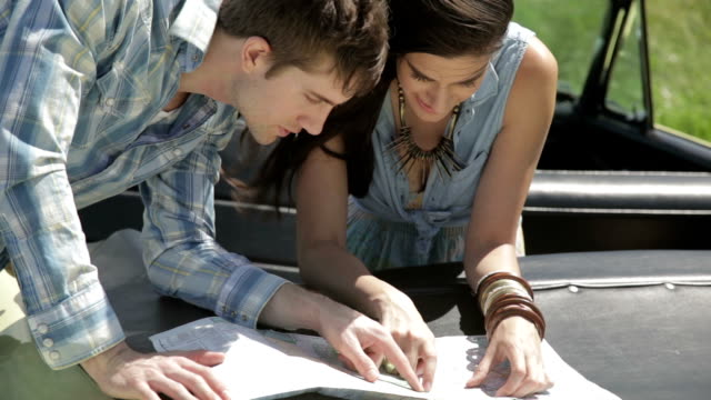 stockvideo's en b-roll-footage met young couple searching for directions using a map on car - roadmap