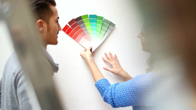 Young couple selecting paint colour in new home video