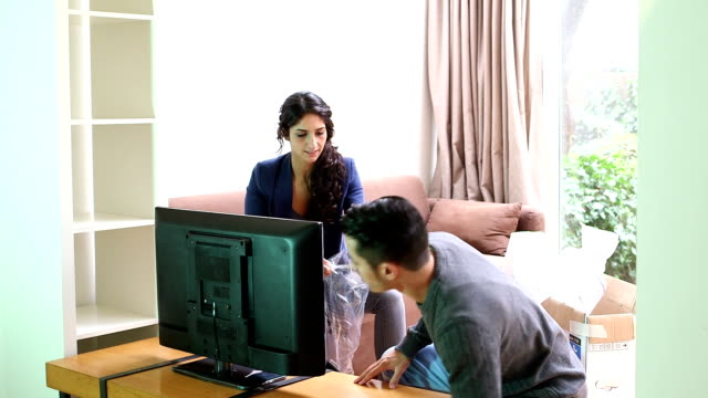 Young couple set new LCD television in living room video