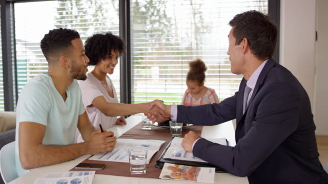 young couple shaking hands with a personal banker at a meeting in their home - risparmi video stock e b–roll