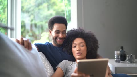 stockvideo's en b-roll-footage met jonge paar delen digitale tablet leggen in couch - huiselijk leven