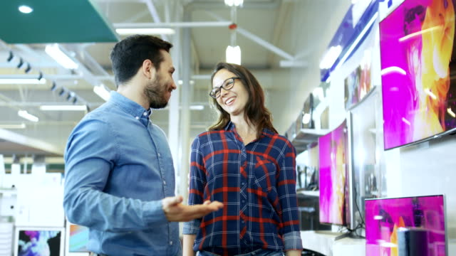 Young Couple Shopping for a New 4K TV Set in the Electronics Store. They're Trying to Decide on the Best Model But Have Doubts. Young Couple Shopping for a New 4K TV Set in the Electronics Store. They're Trying to Decide on the Best Model But Have Doubts. electronics store stock videos & royalty-free footage