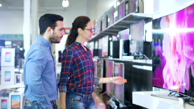 vídeos de stock e filmes b-roll de young couple shopping for a new 4k uhd television set in the electronics store. they're deciding on the best model for their happy family house. - tv e familia e ecrã