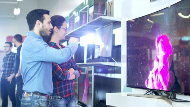 young couple shopping for a new 4k uhd television set in the electronics store. they're deciding on the best model for their happy family house. - электрическое оборудование стоковые видео и кадры b-roll