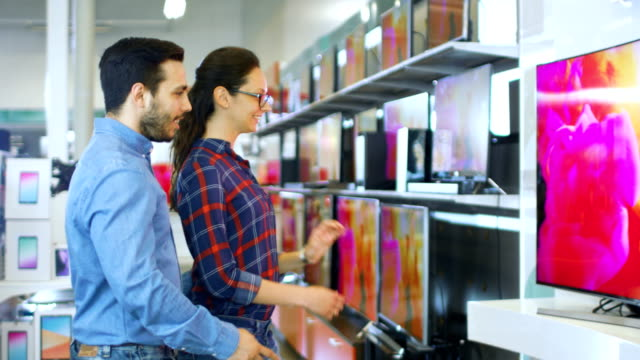 Young Couple Shopping for a New 4K UHD Television Set in the Electronics Store. They're Deciding on the Best Model for Their Happy Family House.