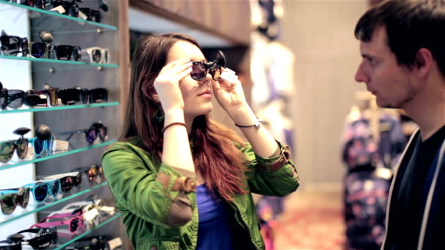 young couple shopping in store, looking for sunglasses, discussing - solglasögon bildbanksvideor och videomaterial från bakom kulisserna