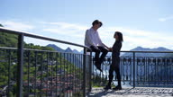 istock Young couple sit at view point talking to each other 1319755778