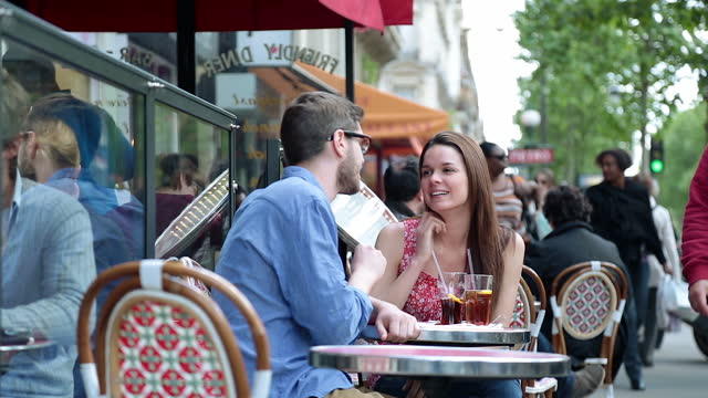 Young couple sit outside and chat over drinks at quaint Parisian diner on the Boulevard Saint-Germain. A couple laughs over drinks in a pub in Paris. european culture stock videos & royalty-free footage