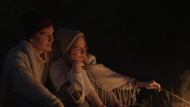 a young couple sits at night in the forest, embracing under a common plaid in front of a bonfire, talking and laughing - falò spiaggia video stock e b–roll
