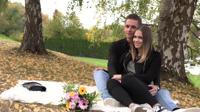 stockvideo's en b-roll-footage met een jong koppel zit op een witte bedspread in herfst park - sober leven