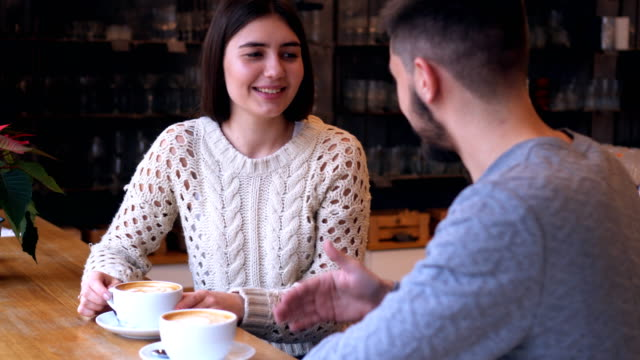 Young couple sitting at cafe talking to each other video