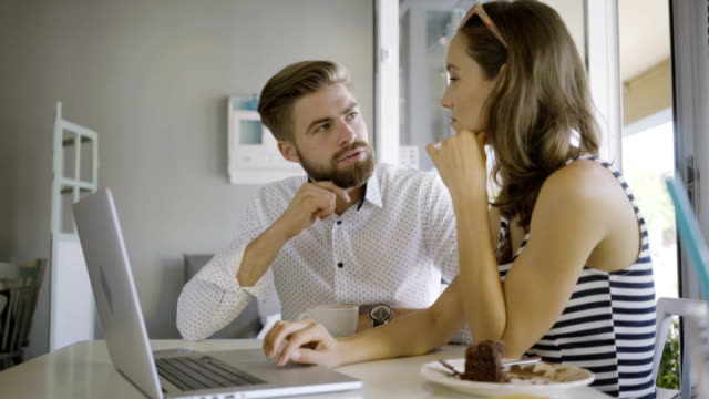 Young couple sitting in a cafe and looking at laptop discussing vacation plans