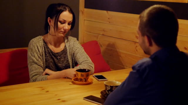 Young couple sitting in a cafe at a table drinking coffee and talking. Girl face smiling. Two lovers enjoy the evening video