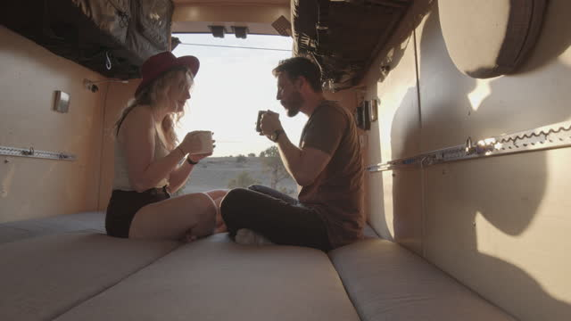 Young Couple Sitting In Their Conversion Van, Talking And Drinking A Cup Of Coffee As The Sun Is Setting