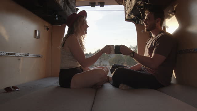 Young Couple Sitting Legs Crossed In Their Camper Van, Making A Celebratory Toast With Their Coffee Mugs As The Sun Is Setting