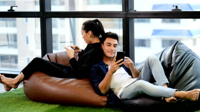 Young couple sitting on bean bags using mobile phone Young couple sitting on bean bags using mobile phone back to back stock videos & royalty-free footage
