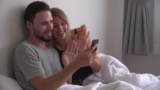 Young couple sitting on bed making video call on mobile phone