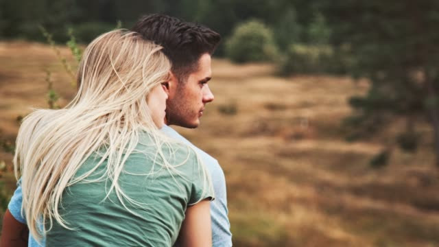 Young couple sitting on field during vacation