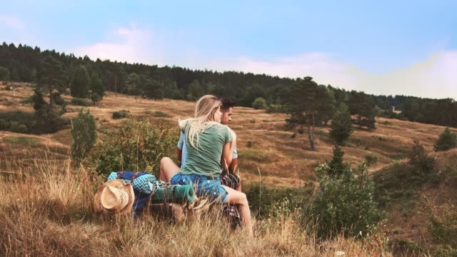 Young couple sitting on meadow during vacation
