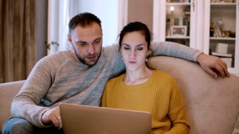 vidéos et rushes de jeune couple assis sur le canapé et la tenue informatique. homme et femme à l'aide d'ordinateur portable tout en étant assis au salon - jeune couple