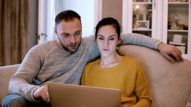 Young couple sitting on the couch and holding computer. Man and woman using laptop while sitting at living room Young beautiful couple sitting on the couch and holding computer. Man and woman spending time together, surfing the Internet. Using laptop while sitting at living room and talking with each other. web browser stock videos & royalty-free footage
