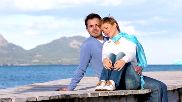 young couple sitting on the jetty video