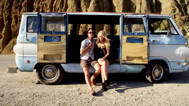 Young couple sitting together by old van video