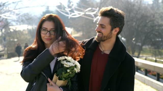 young couple smiling at camera with flowers bouquet and flirting. - flirtować filmów i materiałów b-roll