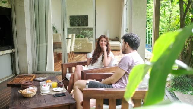 vídeos de stock e filmes b-roll de young couple spending leisurely weekend morning on deck - mesa mobília