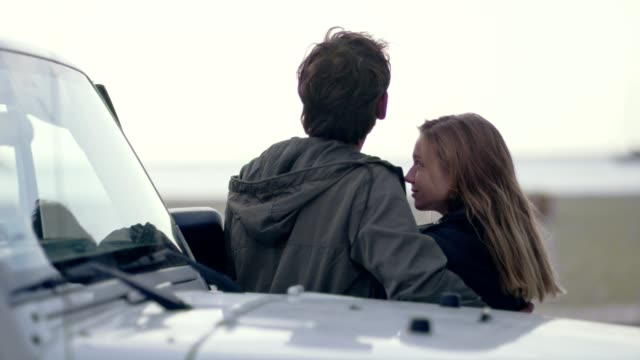 vidéos et rushes de jeune couple de passer du temps romantique sur la plage - homme faire coucou voiture