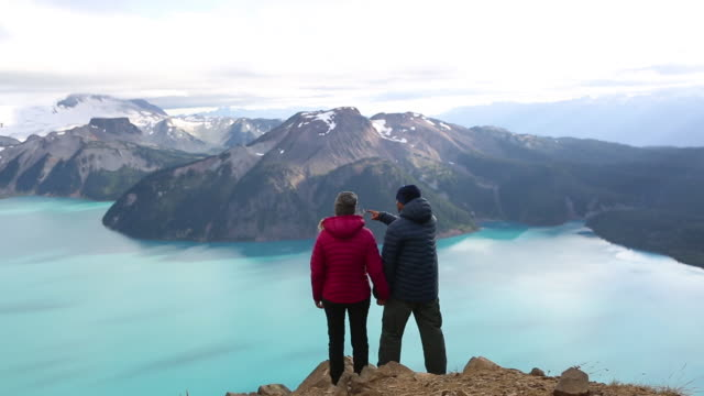 Young couple stand on a mountain top and admire the view video