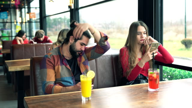 Young couple staring at their phones in distress Eskişehir City Turkey Couple sitting in cafe telefone stock videos & royalty-free footage