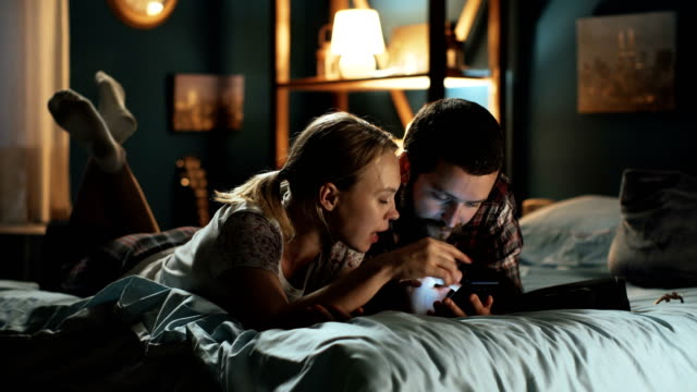 young couple surfing smartphone on bed - comodità video stock e b–roll