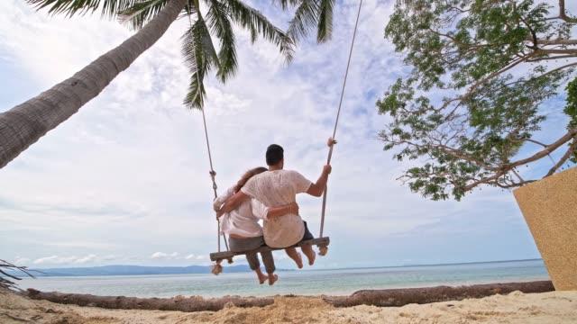 ein junges ehepaar schwingt auf einer schaukel an einem tropischen strand. das verliebte paar an einem strandschaukel am meer in südostasien. - schaukel stock-videos und b-roll-filmmaterial