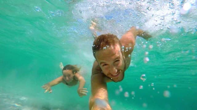 young couple take selfie portrait underwater with action camera - nuoto mare video stock e b–roll