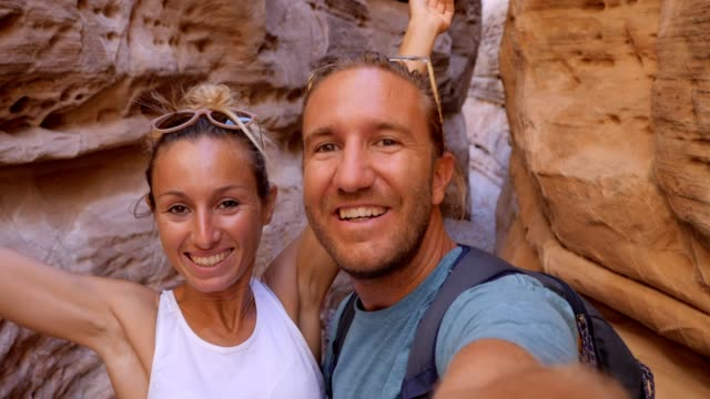 young couple takes selfies inside a narrow canyon - red rock canyon national conservation area video stock e b–roll