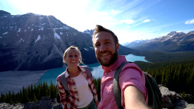 young couple taking a selfie in canada by stunning mountain lake - canada travel stock videos and b-roll footage