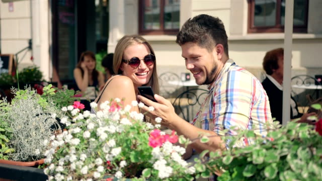 Young couple taking a selfie together on the cafe terrace on sunny day video