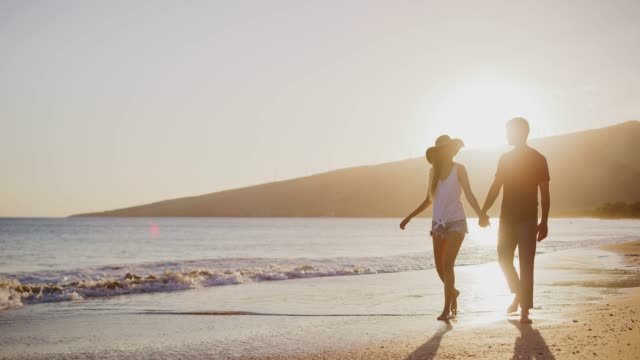 Young couple taking a sunset beach walk video