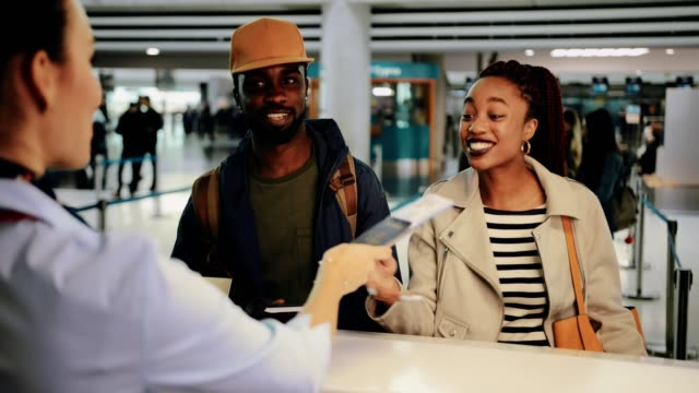 young couple taking boarding passes at airport check-in desk - wchodzić na pokład filmów i materiałów b-roll