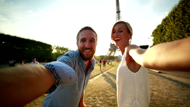 young couple taking selfie at the eiffel tower-paris pov - paris fashion stock videos and b-roll footage