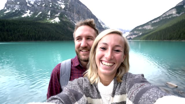 young couple taking selfie portrait at lake louise - canada travel stock videos and b-roll footage