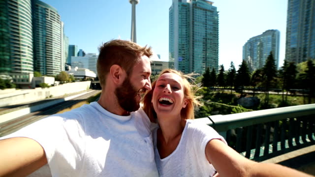 young couple taking selfie portrait in toronto-summer - toronto architecture stock videos & royalty-free footage