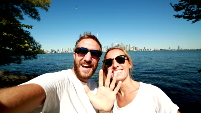 young couple taking selfie portrait in toronto-summer - canada travel stock videos and b-roll footage