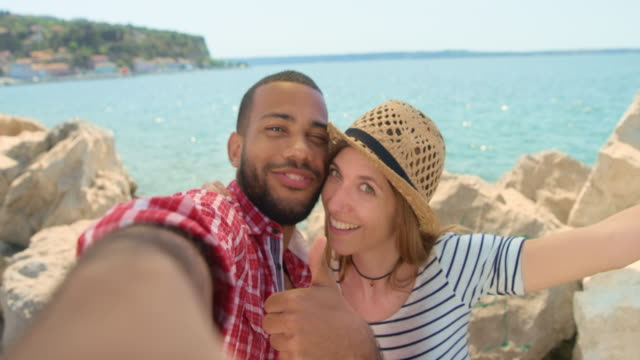 Young couple taking selfies by the sea