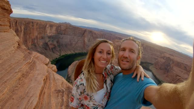 Young couple taking selfies in wester USA. People travel concept. Couple takes selfies at horseshoe bend in Arizona. Spectacular canyon formation, selfie time