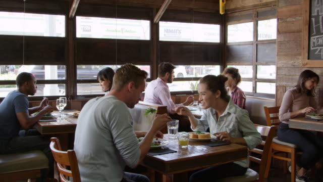 Young couple talking over lunch in a restaurant, R3D video